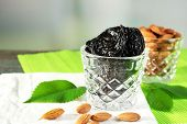 image of prunes  - Prunes and almonds in glasses with leaves on green napkin - JPG