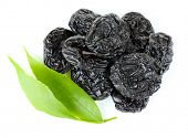 pic of prunes  - Pile of prunes with green leaves isolated on white - JPG