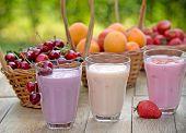 picture of yogurt  - Fruit yogurt (yogurts) and fruits on table ** Note: Shallow depth of field - JPG