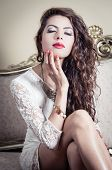 stock photo of bolivar  - Pretty model girl wearing white dress sitting on victorian sofa posing for camera with eyes closed - JPG
