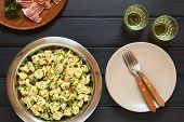 picture of dark side  - Tortellini salad with green peas fried bacon and parsley in big salad bowl with plates forks and two glasses of white wine on the side photographed overhead on dark wood with natural light - JPG