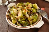 pic of brussels sprouts  - A dish of fried brussels sprouts on a rustic wooden table - JPG