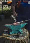 picture of blacksmith shop  - Blacksmith forges iron on anvil - JPG