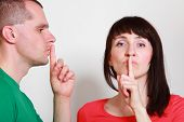 image of silence  - Woman and man showing hand silence sign couple showing silence sign holding index finger to lips - JPG
