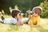 foto of binoculars  - Two little boys play with binoculars on the grass - JPG