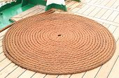 stock photo of roping  - Old nautical thick rope wrapped in spiral lying on weathered deck of yacht circle of thick rope - JPG