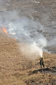 picture of fire  - A wildland fire figher moves a fire hose up a hill to extinquish a small grass fire during fire season in Oregon