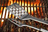 image of flipper  - BBQ Tools Spatula Flipper Fork On The Hot Flaming Charcoal Grill Background - JPG