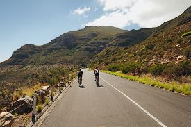 picture of triathlon  - Rear view of two cyclist riding down the country road through mountains - JPG