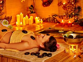 picture of stone-therapy  - Woman getting stone therapy massage in bamboo spa - JPG