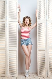 picture of jalousie  - Young beautiful woman wearing shorts and  stripy top posing in front of a jalousie - JPG