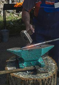 stock photo of anvil  - Blacksmith forges iron on anvil - JPG