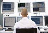 pic of computer-screen  - Stock Trader Looking At Multiple Monitors - JPG