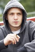 stock photo of teen smoking  - Young Man Sitting In Playground Smoking Joint - JPG