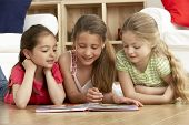stock photo of 7-year-old  - Three Young Girls Reading Book at Home - JPG