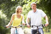 picture of portrait middle-aged man  - Couple riding bikes in countryside - JPG
