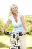stock photo of middle-age  - Portrait of mature woman riding cycle in countryside - JPG