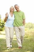 stock photo of middle-age  - Mature couple walking in countryside - JPG