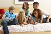 Group Of Five Teenage Friends Hanging Out In Bedroom