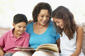 Grandmother Reading With Grandchildren At Home Together