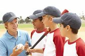 stock photo of hitter  - Young Boys In Baseball Team With Coach - JPG