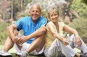 Senior Couple Resting Aftre Exercising In Park