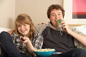 Teenage Couple Sitting On Sofa Watching TV