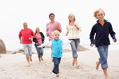 Three Generation Family Running Along Winter Beach Together
