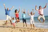 stock photo of beach holiday  - Portrait Of Three Generation Family On Beach Holiday Jumping In Air - JPG