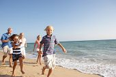 stock photo of extended family  - Portrait Of Three Generation Family On Beach Holiday - JPG