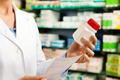 Female pharmacist �¢�?�? only hands to be seen �¢�?�? standing in pharmacy with pharmaceuticals