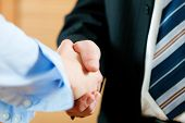 Two businessperson shaking hands; only hands to be seen