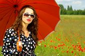 Beautiful happy young brunette with orange umbrella