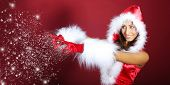 picture of hottie  - Attracive girl in santa cloth blowing snow from hands - JPG