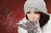 foto of hottie  - Attracive girl in santa cloth blowing snow from hands - JPG