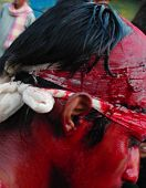 stock photo of muharram  - A shia muslim in lucknow india with blood drenched face after cutting his head for mourning the 40th day of martyrdome of Imam Hussain at Karbala Iraq some 1400 years ago - JPG