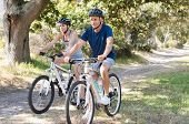 Active senior couple riding bikes during vacation. Happy mature couple cycling through the park. Ret poster