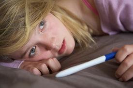 stock photo of pregnancy test  - Depressed Teenage Girl Sitting In Bedroom With Pregnancy Test - JPG
