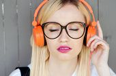 Постер, плакат: Girl Listening To Music Girl Enjoying Music Relaxing Orange Headphones Street Shoot Music Energ