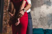 Cropped Shot Of Man Putting Handcuffs On Sensual Woman In Red Dress poster