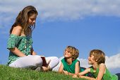 stock photo of storytime  - happy smiling family relaxing and reading outdoors in summer - JPG