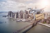 unmanned Multicopter drone flying with package over lower Manhatten, New York City poster