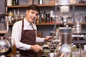 Asian Male Barista Making Coffee In Coffee Shop Counter.  Barista Male Working At Cafe. Man Working  poster