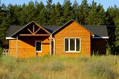 Wooden House In Countryside. Ecological Small Wooden House. Wooden House With Meadow In Front Of It. poster