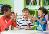 Group Of Diversity Kids Boy Sit On Table And Playing Together In Preschool Library,kindergarten Scho poster
