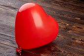 Heart Shaped Balloon On Wooden Background. Red Balloon In A Shape Of Heart Filled With Oxygen On Bro poster