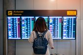 Постер, плакат: Young Woman Traveler With Backpack And Luggage Looking At Boarding Time At Departure Board At Termin