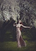 Beautiful Young Woman With Very Long Red Hair In A Golden Dress Under A Flowering Tree , Walking Thr poster