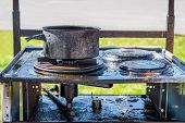 Close Up Of A Burnt Black Gas Stove Covered With Grease, A Burnt Pot On Top. poster
