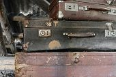 Two Old, Rusty, Dusty And Dirty Brown And Black Suitcases Lying On The Brown Chest In Attic poster
